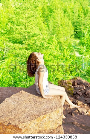 Young redhead curly woman sitting on cliff's edge and looking at the camera on  forest background