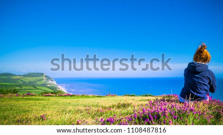 Young redhead girl in trekking clothes is sitting on the top of a hill with purple flowers and sea / English Channel in the front. Golden Cap on jurassic coast in Dorset, UK. Selective focus.