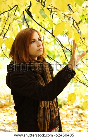 young redhead girl in warm clothes stretch hand to leaves on autumn tree