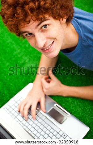 Young redhead guy sitting on the grass with his laptop