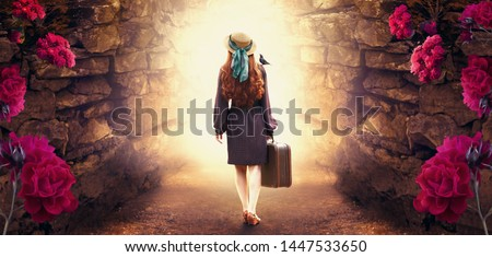 Young redhead lady woman in polka dot dress, hat and suitcase in retro style with starling bird on shoulder walking out through stone dungeon cave towards mystical glow. Idyllic tranquil fantasy scene #1447533650