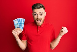 Young redhead man holding 1000 hungarian forint banknotes screaming proud, celebrating victory and success very excited with raised arm