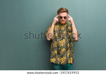 Young redhead man wearing exotic summer clothes doing a concentration gesture