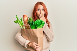 Young redhead woman holding paper bag with bread and groceries covering mouth with hand, shocked and afraid for mistake. surprised expression