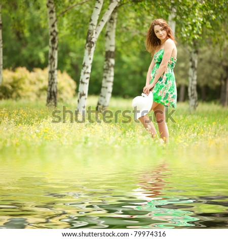 Young redhead woman in the park with flowers