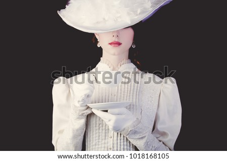 Young redhead woman in white Victorian era clothes with cup of tea on black background.