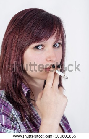 young redhead woman is smoking a cigarette - isolated on white background