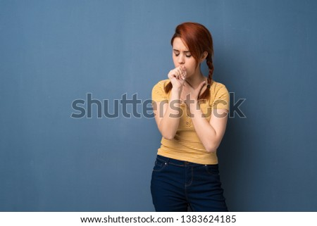 Young redhead woman over blue background is suffering with cough and feeling bad