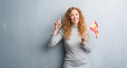 Young redhead woman over grey grunge wall holding flag of Spain surprised with an idea or question pointing finger with happy face, number one