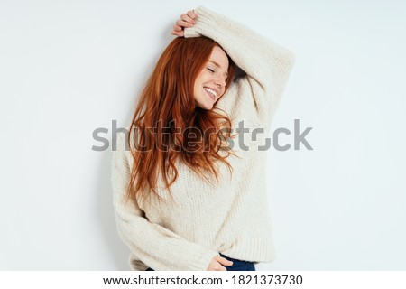 Young redhead woman playing the diva raising her arms languidly above her head with closed eyes and a smile over a white studio background with copy space Foto stock ©