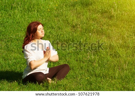 young redhead woman practicing yoga lotus pose outdoors on the grass on the lawn in the park