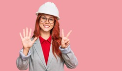 Young redhead woman wearing architect hardhat showing and pointing up with fingers number seven while smiling confident and happy.