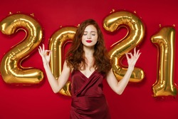 Young redhead woman wearing elegant dress hold hands in yoga gesture relaxing meditating isolated on red background golden numbers air balloons. Happy New Year 2021 celebration holiday party concept