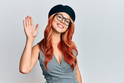 Young redhead woman wearing fashion french look with beret waiving saying hello happy and smiling, friendly welcome gesture