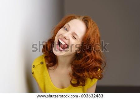 Young redhead woman winking and sticking out her tongue as she teases the camera in a playful mood
