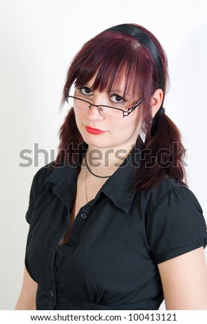 young redhead woman with glasses is looking strict
