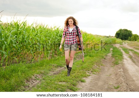 Young redhead woman with guitar passes corn field outdoors in summer by dirt road