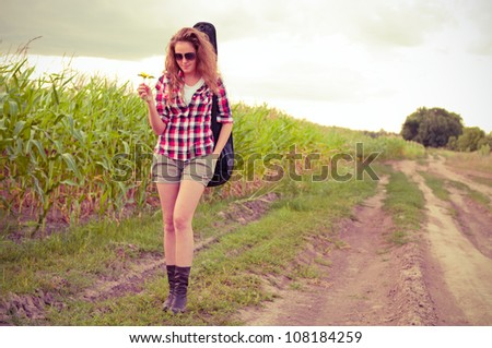 Young redhead woman with guitar passes corn field outdoors in summer by dirt road. Split toning. - stock photo