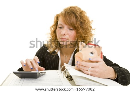 Young redheaded woman holding a piggy bank and using a calculator