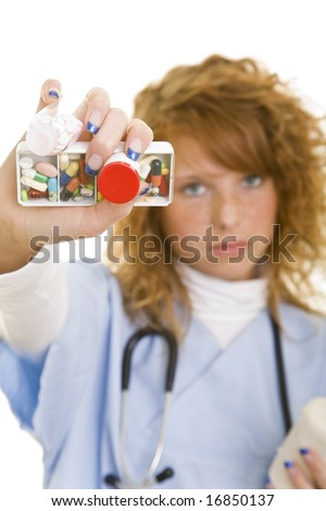 Young redheaded woman wearing a lab coat holding medical supplies