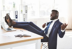 Young relaxed african businessman having fun at office, listening to music and perfoming as playing guitar, putting legs on workdesk, copy space