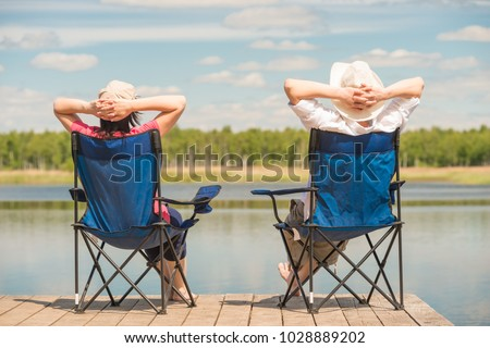 young relaxed couple near a picturesque lake sitting on chairs on a pier