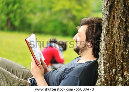 Young relaxed father reading book and children playing around #55080478