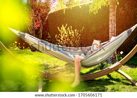Young relaxed girl reading book in hammock in garden at home at bright sunset. Slow living, gadget detox and weekend leisure activity. Quarantine and self isolation period