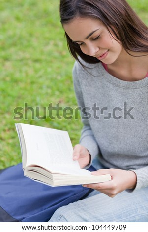 Young relaxed girl sitting on the grass in a parkland while reading a book