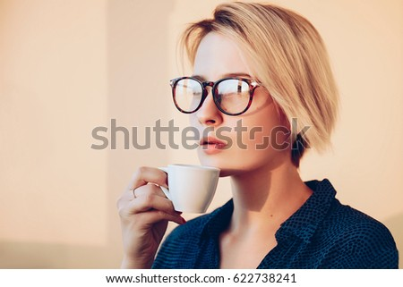 Young relaxed girl with coffee espresso in hand looking out window and thinking . Blonde woman in glasses, short hair style, dressed good. Dreaming concept