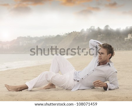 Young relaxed man laying on beach