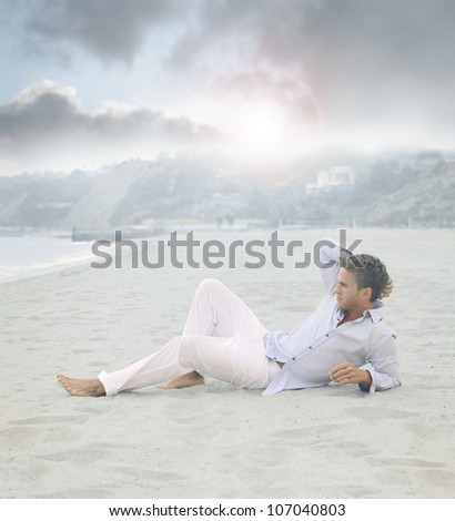 Young relaxed man laying on beach in calm blue morning light