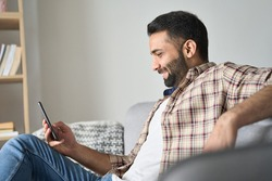 Young relaxed smiling indian man sitting on couch in modern living room looking at cellphone checking social media, surfing internet, ordering food delivery, using mobile apps at weekend at home.
