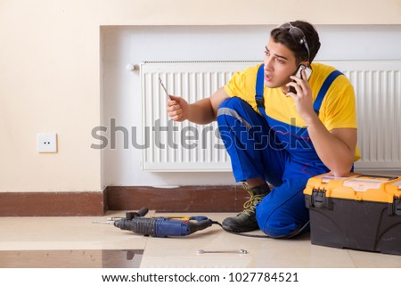 Young repairman contractor repairing heating panel  #1027784521