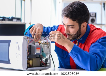 Young repairman fixing and repairing microwave oven #1023508039