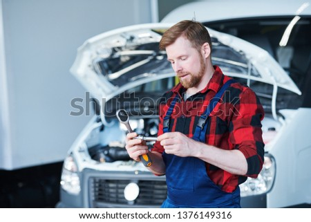 Young repairman in flannel and overalls looking at handtool in his hands on background of car engine #1376149316