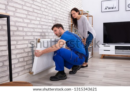 Young Repairman Installing Radiator On Brick Wall With Woman Standing At Home