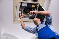Young repairman repairing ceiling air conditioning unit
