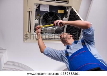 Young repairman repairing ceiling air conditioning unit  #1389662861