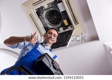 Young repairman repairing ceiling air conditioning unit  #1396123055
