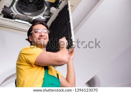 Young repairman repairing ceiling air conditioning unit  #1396123070