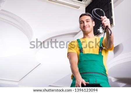 Young repairman repairing ceiling air conditioning unit  #1396123094