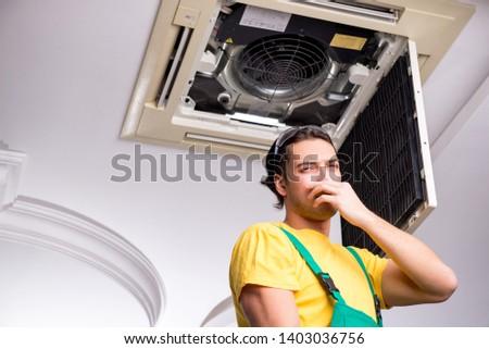 Young repairman repairing ceiling air conditioning unit  #1403036756