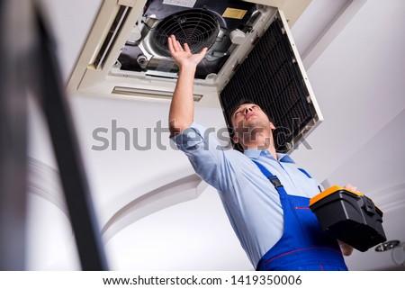 Young repairman repairing ceiling air conditioning unit  #1419350006