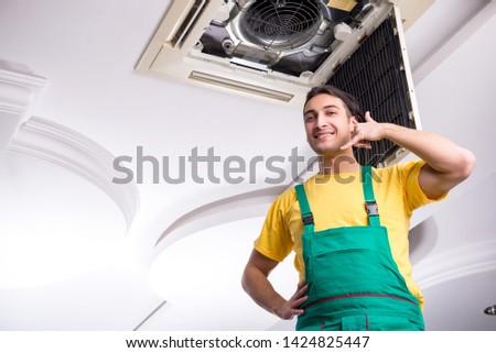 Young repairman repairing ceiling air conditioning unit  #1424825447