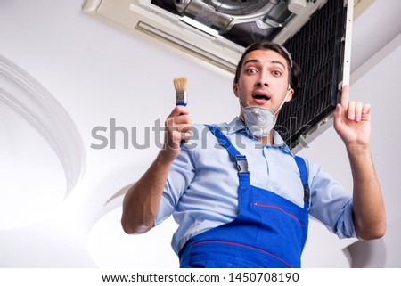 Young repairman repairing ceiling air conditioning unit  #1450708190