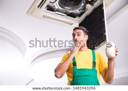 Young repairman repairing ceiling air conditioning unit  #1481943296