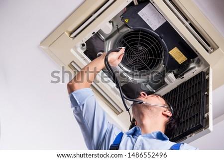 Young repairman repairing ceiling air conditioning unit  #1486552496