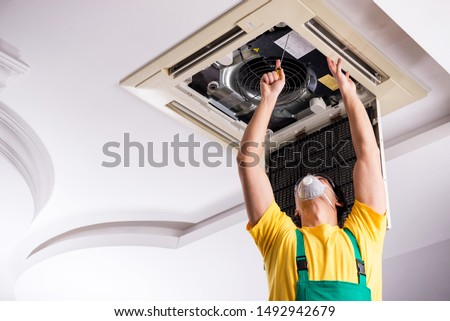 Young repairman repairing ceiling air conditioning unit  #1492942679