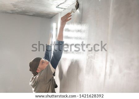 Young repairman smear on wall glue with a brush. Worker glueing wallpapers on concrete wall. Repair the apartment. Home renovation concept. White Wallpaper for paint